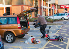 Male loading a diabled persons mobility scooter into the back of. Manchester, UK - January 5th 2015: Male loading a diabled persons mobility scooter into the Royalty Free Stock Images