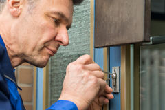 Male Lockpicker Fixing Door Handle At Home. Mature Male Lockpicker Fixing Door Handle At Home Stock Photos