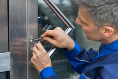 Male Lockpicker Fixing Door Handle At Home. Mature Male Lockpicker Fixing Door Handle At Home Stock Photo