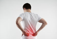 Male loin pain. Lumbago symptom. Young man holding his painful loin Stock Image