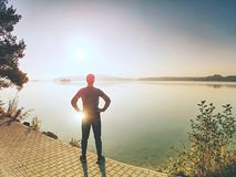 Male long distance runner in endurance training at mountain lake. Short pause. Male long distance runner in endurance training at mountain lake in summer nature stock photography