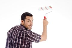 Male looking backward while using roller brush Stock Photo
