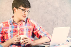 Male looking at laptop closeup. Closeup of caucasian male in vibrant shirt and coffee in hand looking at laptop screen on concrete background Stock Image