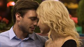 Male looking passionately at woman, couple nuzzling in restaurant, affectionate. Stock footage stock video