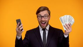 Male looking at smartphone and immediately receiving money cash back application. Stock photo royalty free stock photos