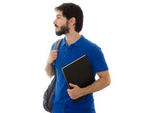 Male looking to the side with backpack and book. College student holds a notebook and a backpack, looking to the side. Profile. Young man wearing blue polo Stock Images