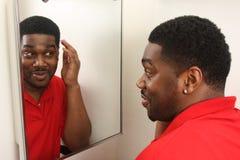 Male looking in vanity mirror Stock Photo
