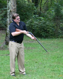 Male looks into the barrel of his shotgun. Adult male looks down into the barrel of his shotgun Stock Photos