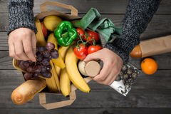 Male looks brown paper bag full of food. On wooden table, top view Stock Photography