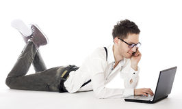 Male lying in front of laptop and calling on mobile phone. Businessman lying in front of laptop and calling on mobile phone. Isolated against a white background Stock Photos