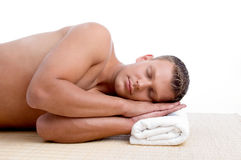 Male lying on mat ready to take spa treatment. Young male lying on mat ready to take spa treatment on an isolated white background Stock Image