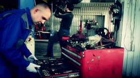 Male maintenance engineer arranging tools in drawer at car workshop. Mechanic working on background under lifted auto stock footage