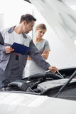 Male maintenance engineer explaining car engine to female customer in repair shop Royalty Free Stock Images