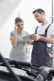Male maintenance engineer showing digital tablet to worried customer at workshop Royalty Free Stock Images