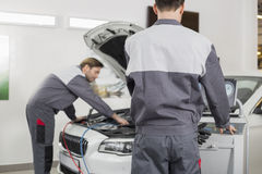 Male maintenance engineers examining car in workshop Royalty Free Stock Photo