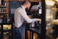 Male is making coffee in a coffee shop. Bearded male is making coffee in a coffee shop Stock Photo