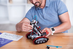 Male making cute small robot on the table Royalty Free Stock Photography