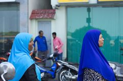 Two maldivian women with a blue veil muslim religion stock photo