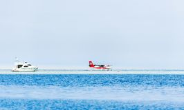 MALE, MALDIVES - NOVEMBER, 27, 2016: Seaplane Trans Maldivian Airways landed on the water. White yacht in the sea. Copy space for. Text royalty free stock photography