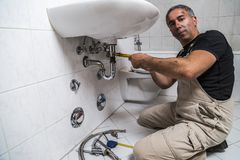 Specialist male plumber repairs faucet in bathroom. Male man dirty muscle inflated worker specialist plumber in black t-shirt and white old shabby working suit Stock Image