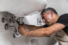 Specialist male plumber repairs faucet in bathroom. Male man dirty muscle inflated worker specialist plumber in black t-shirt and white old shabby working suit Stock Photography