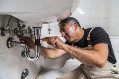Specialist male plumber repairs faucet in bathroom. Male man dirty muscle inflated worker specialist plumber in black t-shirt and white old shabby working suit Royalty Free Stock Photos
