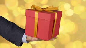 Male man hand holds red gift box with gold bow. Celebrate eve present gift box. Caucasian man in classical suit stock footage