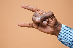 Male, man, hipster, in shirt, hand raised showing a heavy metal rock sign Royalty Free Stock Images