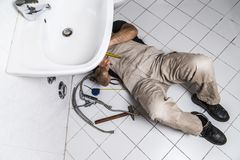 Specialist male plumber repairs faucet in kitchen. Male man young worker specialist plumber in white dirty old shabby working suit, black boots lyes on bathroom Stock Photo