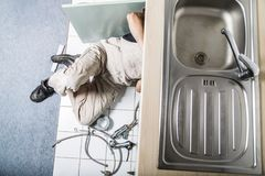 Specialist male plumber repairs faucet in kitchen. Male man young worker specialist plumber in white dirty old shabby working suit, black boots lyes on kitchen Royalty Free Stock Photos