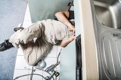 Specialist male plumber repairs faucet in kitchen. Male man young worker specialist plumber in white dirty old shabby working suit, black boots lyes on kitchen Stock Image