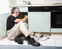 Specialist male plumber repairs faucet in kitchen. Male man young worker specialist plumber in white dirty old shabby working suit, black t-shirt sitting on Royalty Free Stock Photo