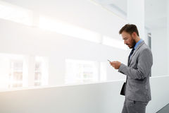 Male manager with cell telephone is standing in office interior near copy space for your advertising content. Worried businessman is reading e-mail on mobile Stock Photo