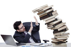 Male manager with falling books on desk Royalty Free Stock Image