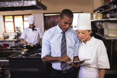 Male manager and female chef using digital tablet in kitchen stock photo
