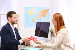 Male manager giving passport with ticket to client royalty free stock photography