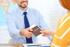 Male manager giving passport with ticket to client royalty free stock photo