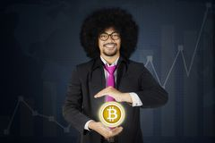 Male manager holding bitcoin symbol. Portrait of Afro male manager holding bitcoin symbol on his hand, shot with virtual financial statistic stock image