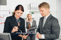 Male manager instructs female employee. Manager instructs employee in office Royalty Free Stock Photo