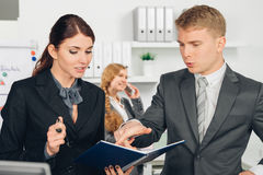 Male manager instructs female employee in office Stock Photo