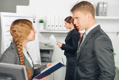 Male manager instructs female employee. Manager instructs employee in office Stock Image