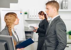 Male manager instructs female employee. Manager instructs employee in office Royalty Free Stock Image