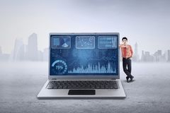 Male manager leans on laptop Stock Images