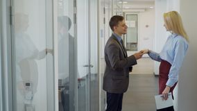 The male manager meets his new female colleague in the bright office corridor. The boss greets the secratary and shakes her hand. The professional wears suit stock footage