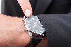 Male manager pointing watch in closeup. As deadline concept Stock Photography