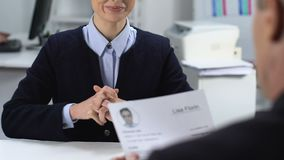 Male manager reading cv female job applicant, smiling woman looking interviewer