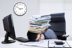 Male manager sleeping with documents. Photo of a male manager sleeping on the table with a pile of documents on his head Stock Photo
