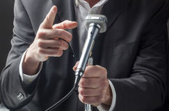 Male manager speaking to a microphone with hand gestures. Business or politician presentation with micro Royalty Free Stock Images