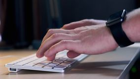 Male manager typing on the keyboard in the office in the evening. A smart watch is worn on the hand. Close-up. Male manager typing on the keyboard in the office stock footage