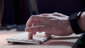 Male manager typing on the keyboard in the office in the evening. A smart watch is worn on the hand. Close-up. Male manager typing on the keyboard in the office stock video footage